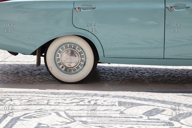 Detail of rear quarter panel, whitewall tires and chrome hubcap of vintage car
