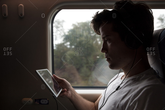 Passenger on train watching movie on tablet computer