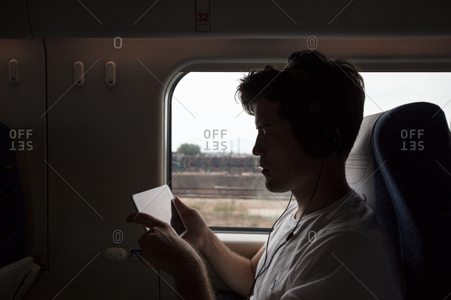 Young man on train passing time on tablet computer