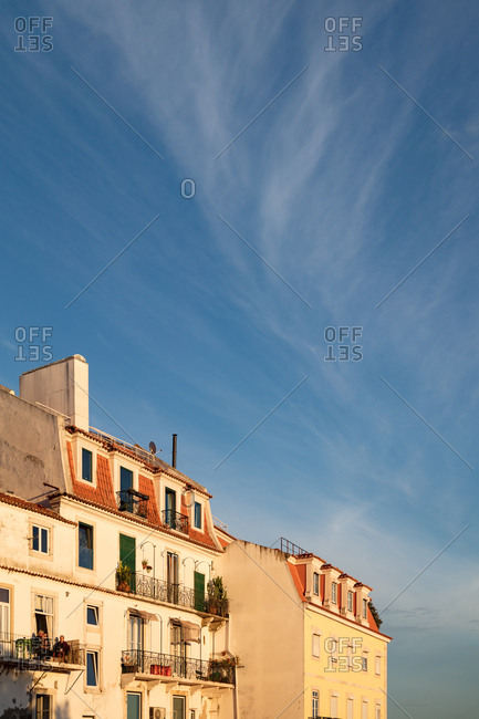 Lisbon, Portugal - 31 July, 2017: Setting sun bathing facade of apartment buildings in warm glow