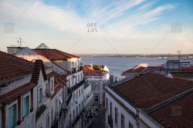 High angle view of narrow alley between apartment buildings leading down to river in Lisbon, Portugal