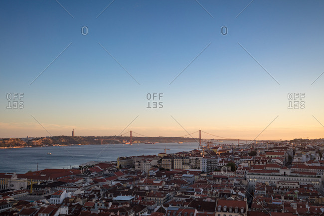 Looking over city towards Sanctuary of Christ the King and suspension bridge over the river Tagus at sunset