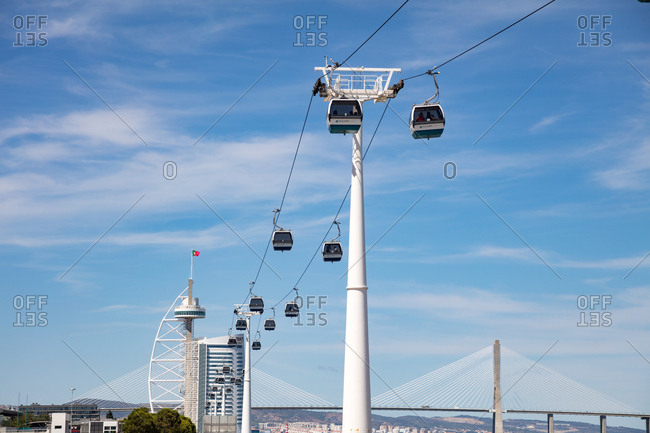 Lisbon, Portugal - 01 August, 2017: Looking up at cable cars suspended above the Parque das Nacoes with Vasco Da Gama Tower in the background