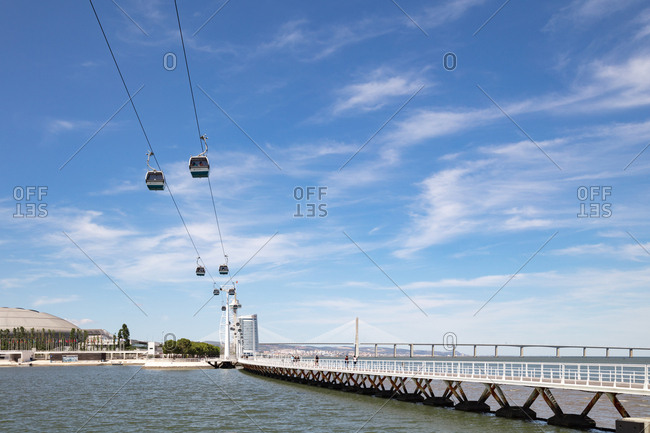 Lisbon, Portugal - 01 August, 2017: Looking up at cable cars suspended above the water with the Vasco Da Gama bridge over the Tagus river in the background