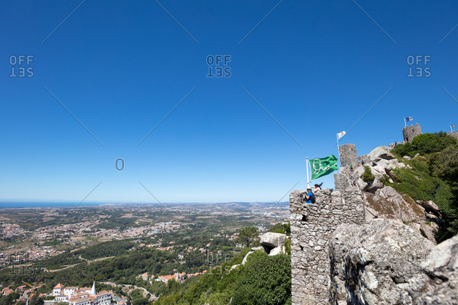 Sintra, Portugal - 02 August, 2017: Tourists on the ramparts of The Castle of the Moors looking out over the landscape