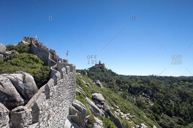 Sintra, Portugal - 02 August, 2017: Looking over rampart of The Castle of the Moors on hilltop towards Pena Palace