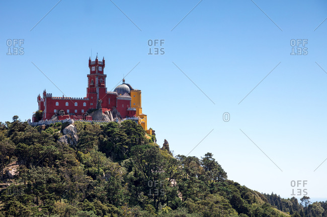 View of multicolored Pena Palace perched on tree covered hilltop above Sintra, Portugal