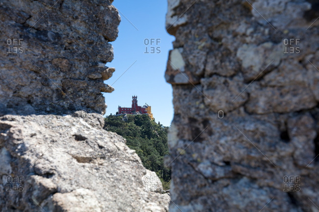 Looking through crenellation of The Castle of the Moors on hilltop towards Pena Palace