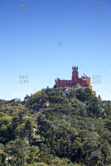 Looking up at multicolored Pena Palace perched on tree covered hilltop above Sintra, Portugal
