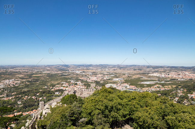 Elevated wide angle view over battlements of The Castle of the Moors on hilltop overlooking landscape beyond