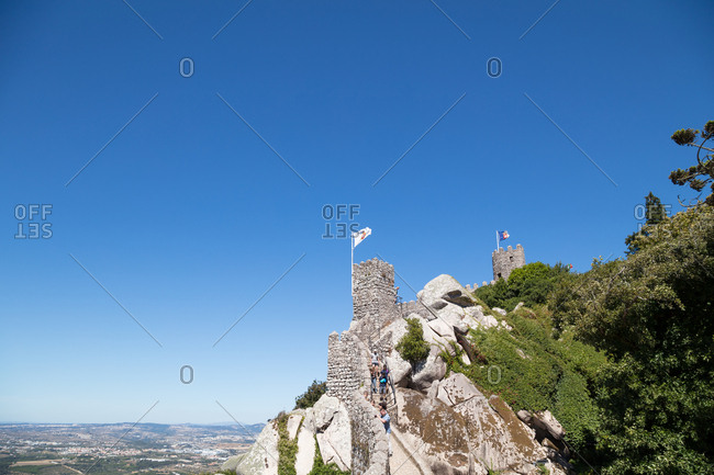 Tourists walking along the battlements of hilltop Castle of the Moors in Sintra, Portugal