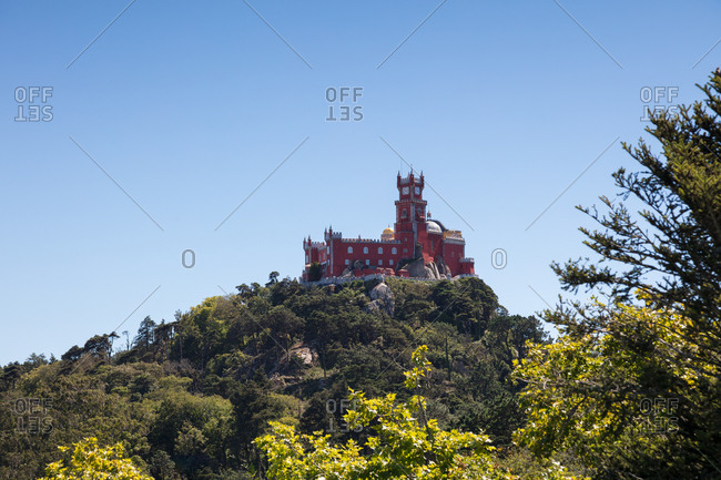 Pena Palace sitting on tree covered hilltop above Sintra, Portugal