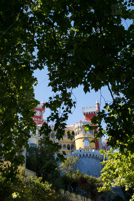 Sintra, Portugal - 02 August, 2017: Looking up through the trees at the colorful towers and facade of Pena Palace