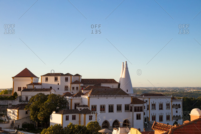 Setting sun highlighting the Moorish facade of the National Palace of Sintra, Portugal