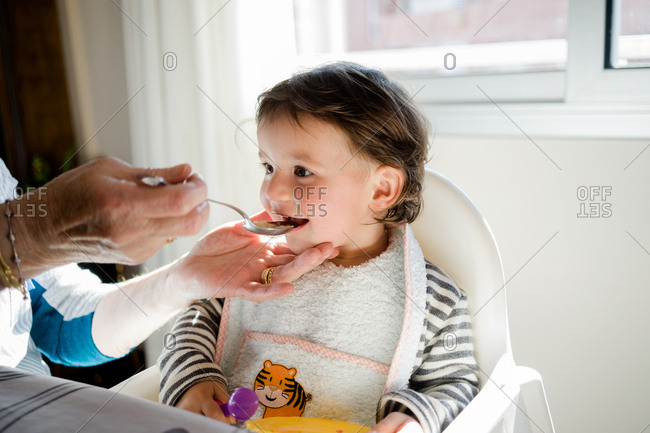 Grandmother's hands spoon-feeding pleased toddler in highchair