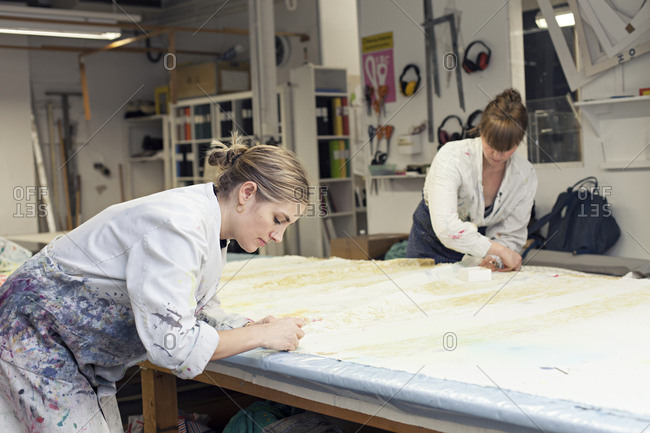 Textile designers securing fabric to work surface before printing