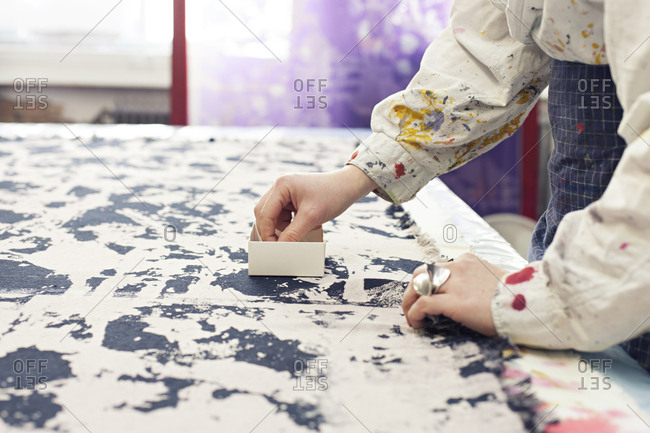 Textile designer pinning fabric together on work surface in studio