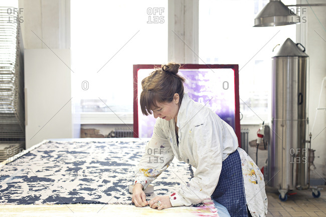 Textile designer working with piece of material on work surface in studio