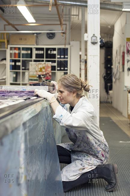 Textile designer kneeling to examine fabric after screen printing in studio