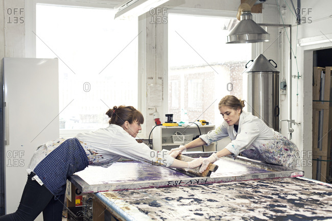 Textile designers using squeegee together to apply ink to stencil in studio