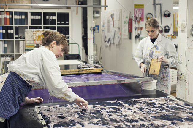 A textile designer checking printed fabric while partner cleans squeegee in studio