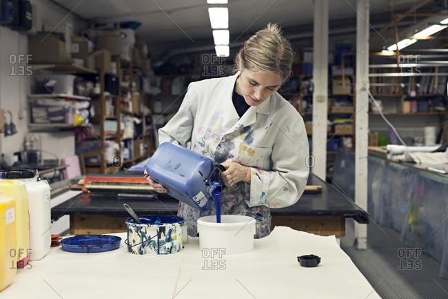 Textile designer preparing ink for screen printing process in studio