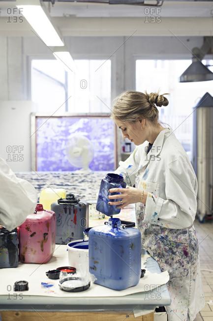 Woman preparing ink for screen printing in textile design studio