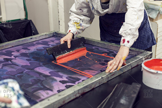 Textile designer applying ink to stencil with squeegee in studio