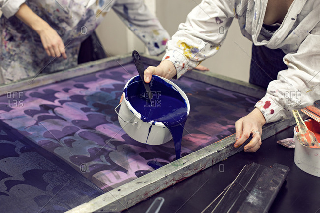 Textile designer pouring ink onto stencil as partner holds screen print stencil in studio