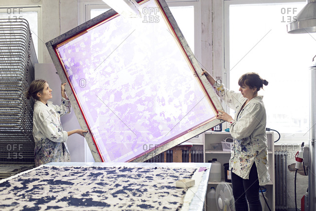 Textile designers working together to move large screen printing frame into place in studio