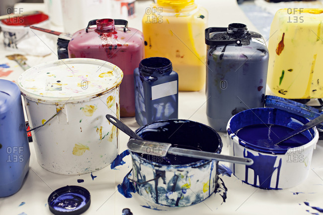 Tubs, jugs and pots of multi colored inks laid out on workshop in textile designer's studio