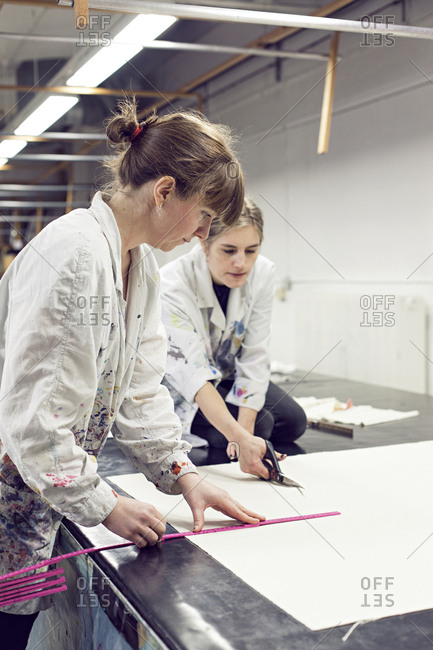 Textile designer measuring fabric as partner cuts it to size in studio