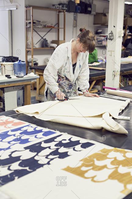 Textile designer cutting fabric to test colors in studio