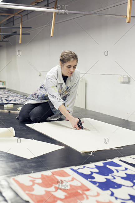 Textile designer kneeling on work surface cutting fabric to size in studio