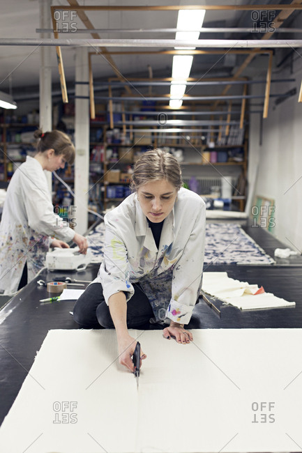 Textile designer cutting fabric to size as partner works in background in studio