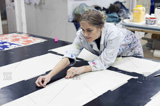 Textile designer taping down fabric to work surface in studio