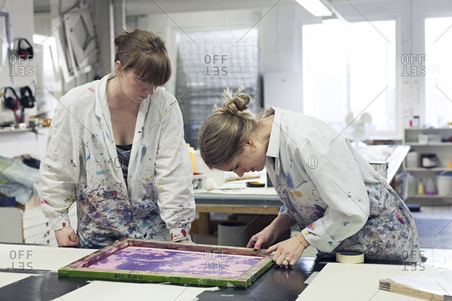 Textile designers working together to position stencil for screen printing on fabric in studio