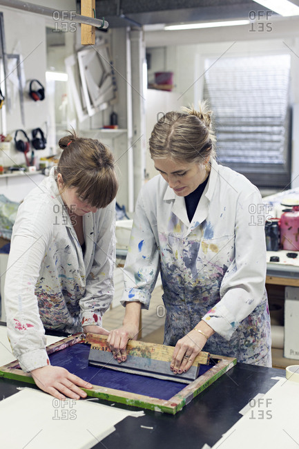 Textile designer holding down stencil as partner applies ink with squeegee in studio