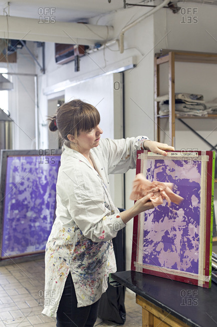 Textile designer wiping down stencil for screen print in studio
