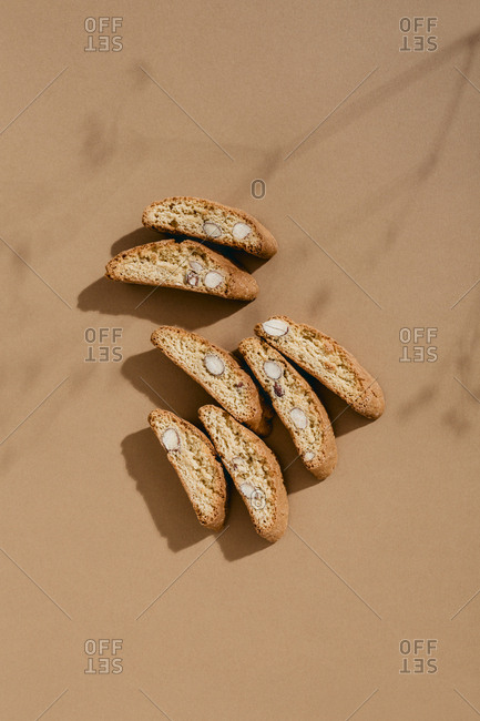 Top down view of shadow of tree branch cast over arrangement of almond biscotti