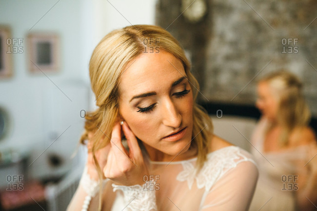 Bride putting on earrings before ceremony