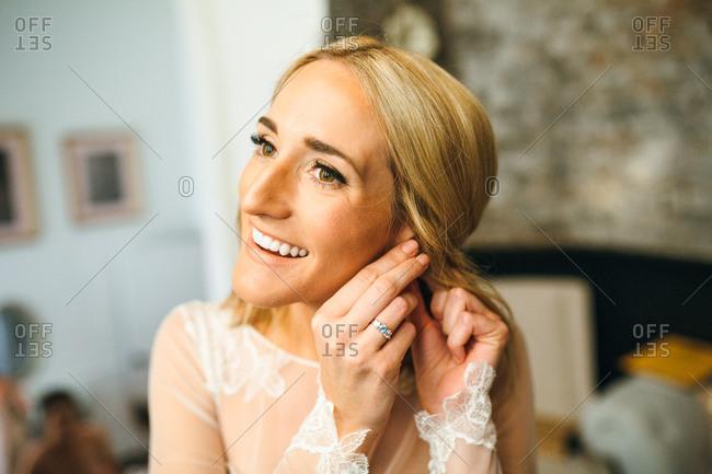 Smiling bride putting in earrings on wedding morning