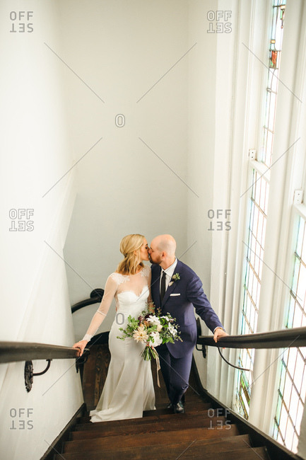 Wedding portrait on staircase with stained glass windows