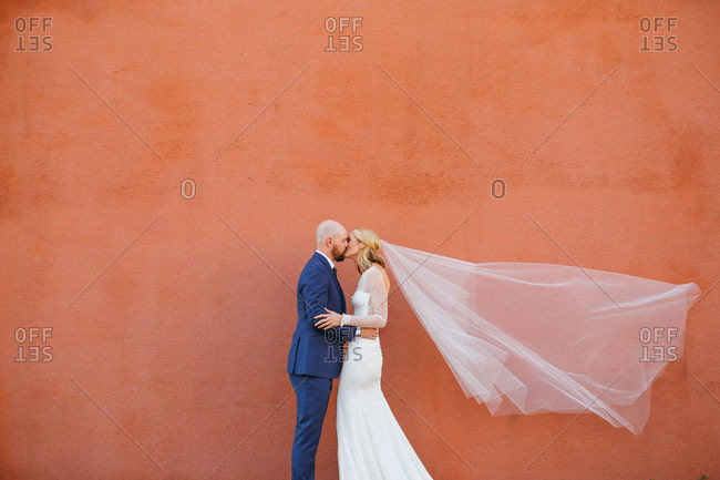 Bride and groom kissing in front of colorful wall