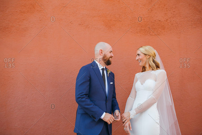 Husband and wife smiling at each other in front of exterior wall after wedding ceremony