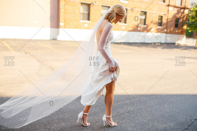 Bride walking through parking lot with gown held up after wedding