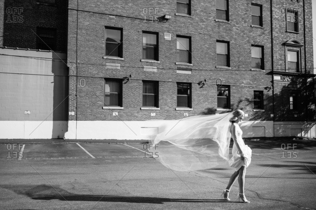 Bride walking across parking lot with breeze blowing long veil behind