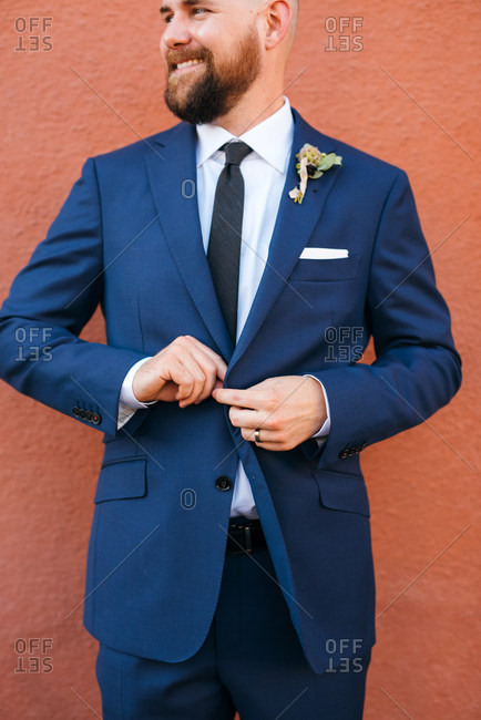 Proud groom buttoning handsome suit jacket