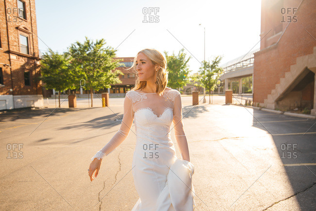 Emotional bride in urban parking lot after wedding ceremony