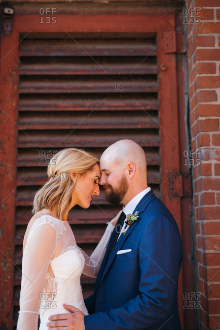 Loving newlywed bride and groom exterior portrait